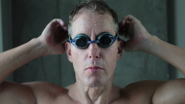 Male swimmer putting on goggles
