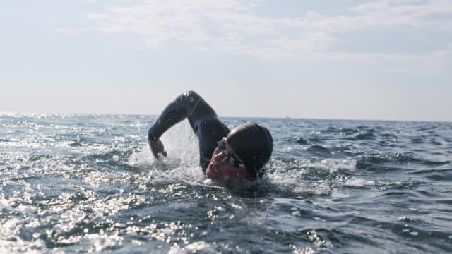 slo mo nuotatore maschio che nuota in avanti strisciando in mare in una giornata di sole - triatleta video stock e b–roll