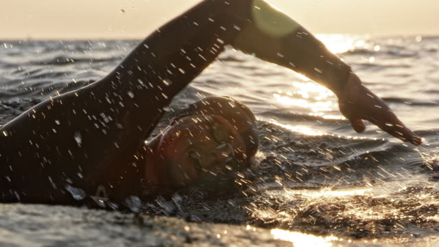 slo mo ts male swimmer swimming front crawl at sea in sunshine - swimming goggles stock videos & royalty-free footage