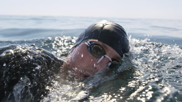 slo mo ts nuotatore maschio che nuota davanti a strisciare sotto il sole - triatleta video stock e b–roll