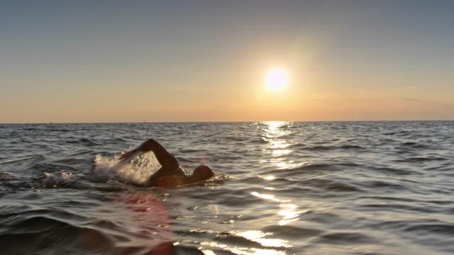 vídeos y material grabado en eventos de stock de nadador de ts hombre nadando crol en el mar agitado al atardecer - reloj de pulsera