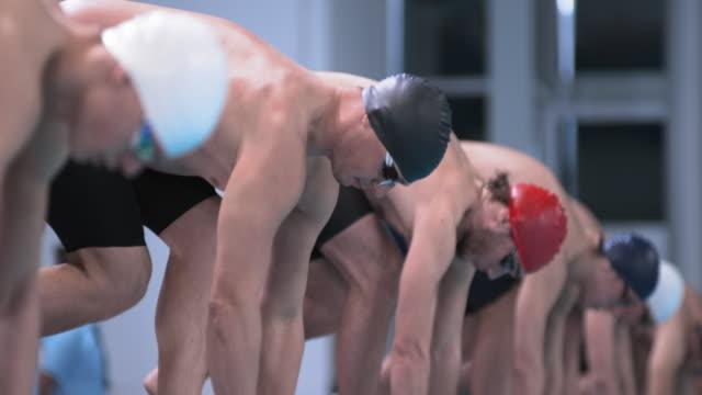 stockvideo's en b-roll-footage met slo mo male swimmers jumping off the starting blocks - binnenbad