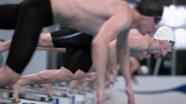 slo mo ds male swimmers starting off the blocks in a competition - people in a line stock videos & royalty-free footage