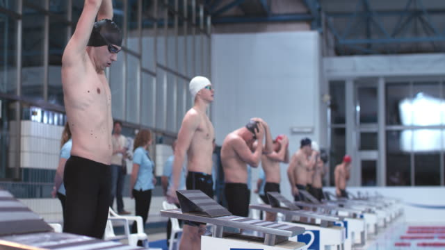 vídeos de stock, filmes e b-roll de ld male swimmers waiting for a start by the starting blocks - touca de natação