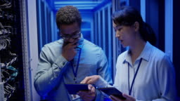 DS Male sysadmin and the Asian female IT engineer checking the servers in the server room