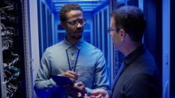 Male sysadmin and the male IT engineer checking the servers in the server room