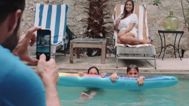 male taking picture of family by the pool at holiday home - sun lounger stock videos & royalty-free footage