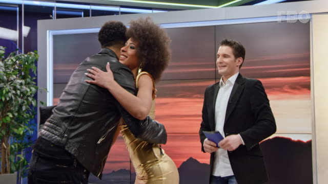 Male talk show host and his guest welcoming a female celebrity entering the studio