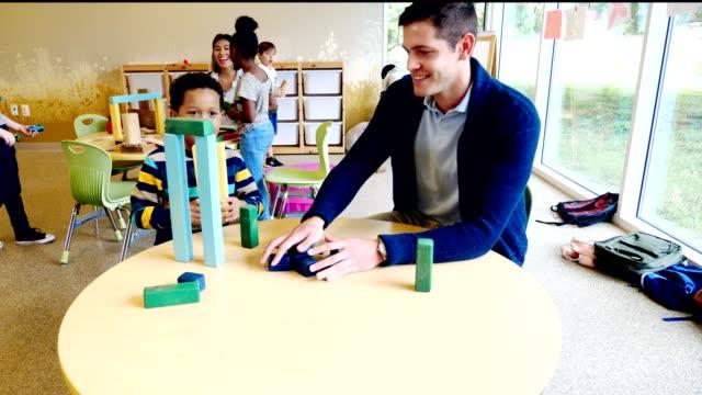 vidéos et rushes de l'enseignant masculin et l'étudiant de jardin d'enfants construisent la structure avec des blocs de jouet - élève du primaire