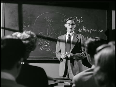 B/W 1949 male teacher at front of high school class talking + pointing to chalkboard / industrial