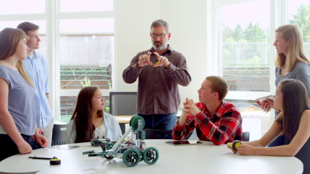 ms male teacher discussing robotics project with students in high school classroom. - female high school student stock videos & royalty-free footage