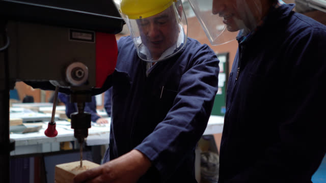 male teacher explaining young student how to use the industrial drill while drilling a wooden block - legno video stock e b–roll