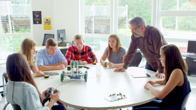 MS male teacher helping high school students work with robot in classroom.