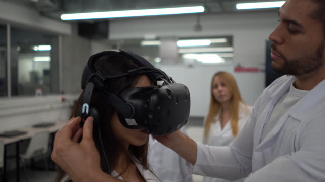 male teacher putting on a vr headset on female student during a design while classmates stand behind her observing - stem stock videos & royalty-free footage