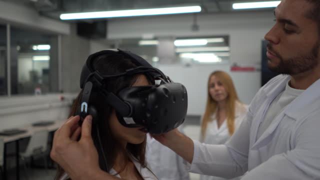männliche lehrerin setzt ein vr-headset auf weibliche schüler während eines designs, während klassenkameraden hinter ihr beobachten stehen - virtuelle realität stock-videos und b-roll-filmmaterial