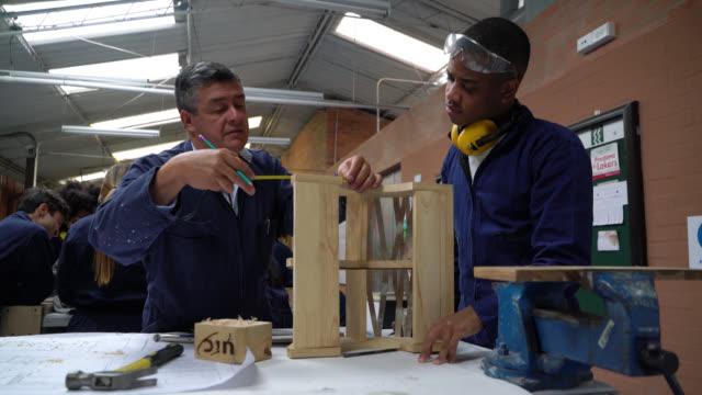 vídeos de stock, filmes e b-roll de professor do sexo masculino que supervisiona as medições sobre projeto de madeira aluno negro está fazendo na aula de oficina - afro
