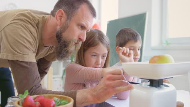vídeos de stock e filmes b-roll de male teacher teaching a pupil how to read the measurements on the kitchen weighing scale - balança instrumento de pesagem