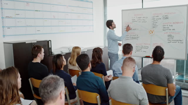 Male teacher teaching adults attending a career course