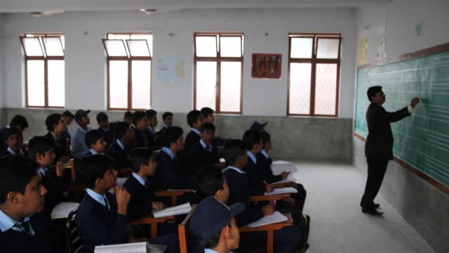 stockvideo's en b-roll-footage met male teacher writing on the blackboard for a class of middle school boys in uniform. - alleen jongens