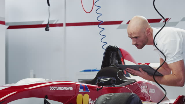 male technician examining racecar at pit stop - examining stock videos and b-roll footage