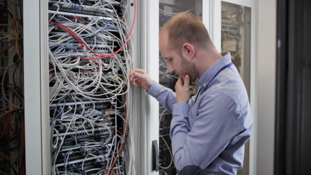 male technician stressing over the cables in the server room - rack stock videos & royalty-free footage