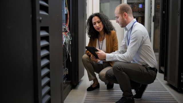 DS Male technician talking to his female colleague in the server room