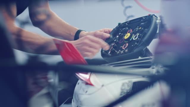 male technician testing steering wheel of racecar - motorsport stock videos & royalty-free footage