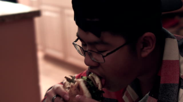 stockvideo's en b-roll-footage met a male teenager eating a burger at home - baseballpet