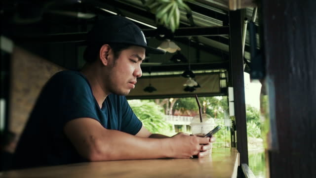 Male teenager typing on mobile phone