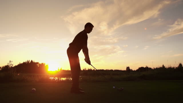 male tees off at sunrise - golf swing stock videos & royalty-free footage