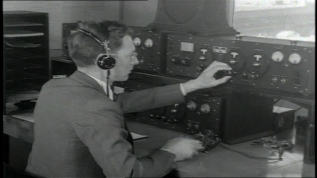 Male telegrapher wearing headset and typing on typewriter / VS Male punching in morse code signals into a 'straight key' telegrapher another male at...
