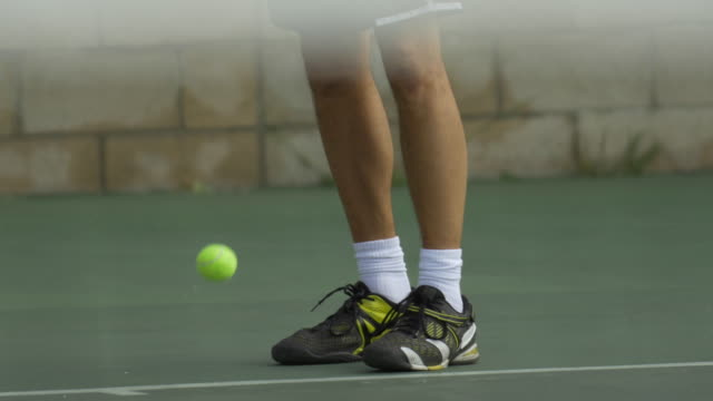 male tennis player bouncing tennis ball with racket. - tennis racket stock videos & royalty-free footage