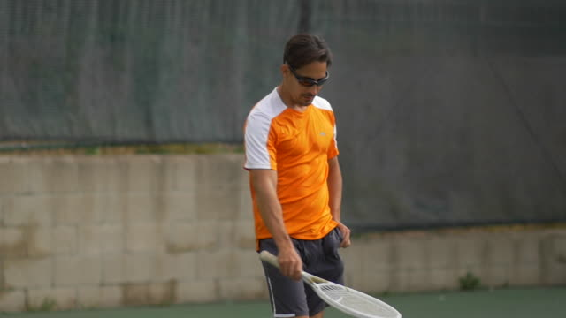 male tennis player gathering tennis balls with racket.  - slow motion - tennis racket stock videos & royalty-free footage