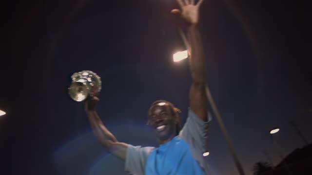 vidéos et rushes de cu, la, male tennis player holding trophy, dusk, santa barbara, california, usa - bras en l'air