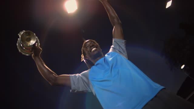 vidéos et rushes de cu, la, canted, male tennis player holding trophy, night, santa barbara, california, usa - bras en l'air