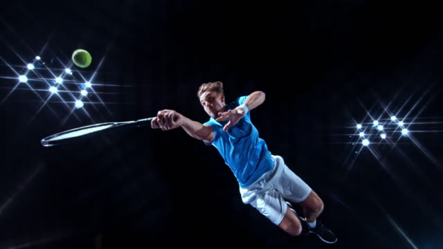 vídeos de stock e filmes b-roll de slo mo male tennis player in a blue jersey jumping in the air and hitting the ball with the racket on a black background - ténis calçado desportivo