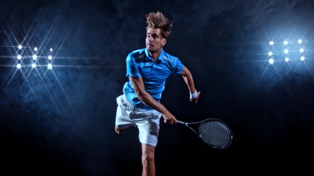 SLO MO Male tennis player in blue jersey hitting the serve on black background