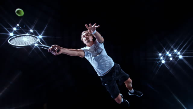 slo mo male tennis player jumping and hitting the ball with the racket on a black background - ボール点の映像素材/bロール