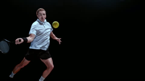 slo mo ds male tennis player striking the ball - black background stock-videos und b-roll-filmmaterial