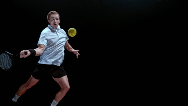 slo mo ds male tennis player striking the ball - colour image stock-videos und b-roll-filmmaterial