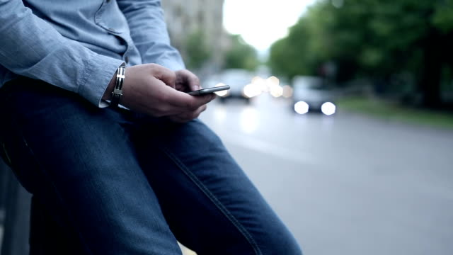 male texting on the street. - bracelet stock videos and b-roll footage