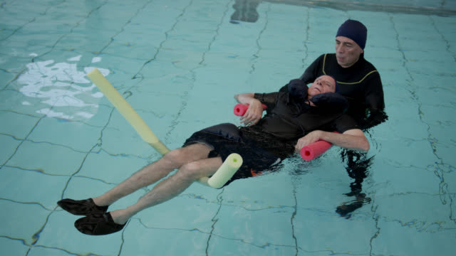 male therapist assisting paraplegic patient during hydrotherapy at a physical rehab clinic - disability services stock videos & royalty-free footage