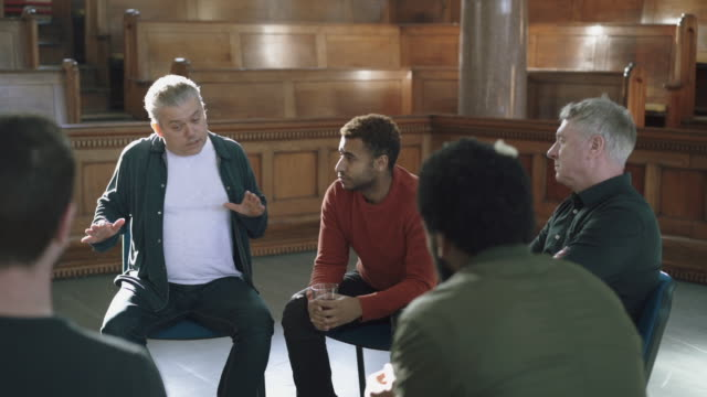 Male therapist talking to other men in support group