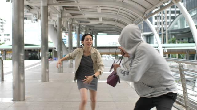 vidéos et rushes de voleur mâle volant le sac de jeune femme asiatique à l'extérieur - sac