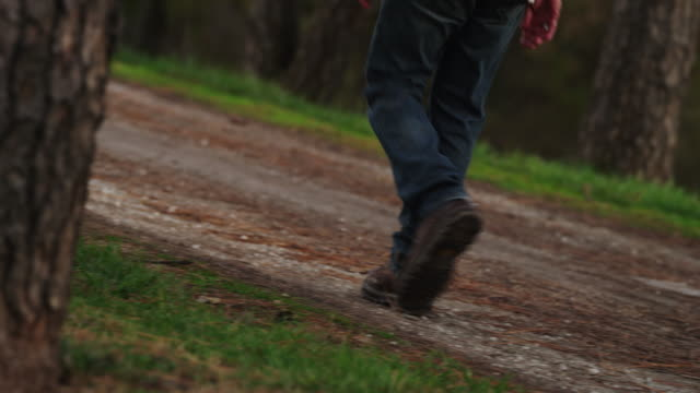 A male torso wearing blue jeans and work boots, walks down gravel road in autumn.