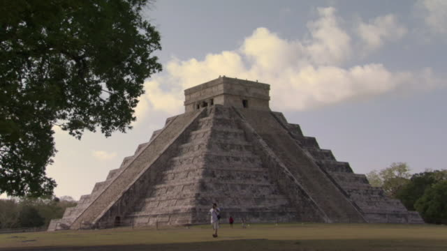 WS Male tourist photographing woman and child near Kukulkan Pyramid at ancient Mayan site Chichen Itza / Yucatan, Mexico