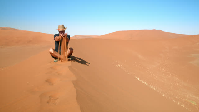 ws male tourist scooping rust colored sand on desert sand dune,namibia,africa - cross legged stock videos & royalty-free footage