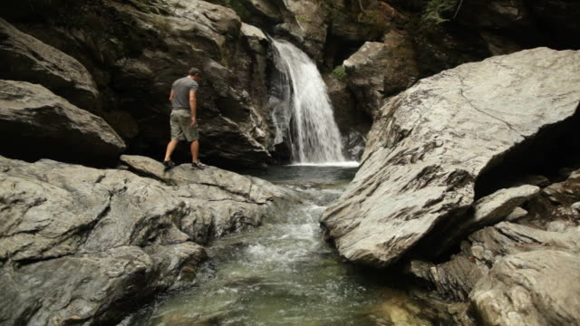 ws male tourist walks across rocks toward waterfall / stowe, vermont, united states - stowe vermont stock videos & royalty-free footage