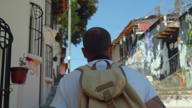 vídeos y material grabado en eventos de stock de male tourist with a backpack exploring a village in san cristobal de las casas, chiapas, mexico - pared de cemento