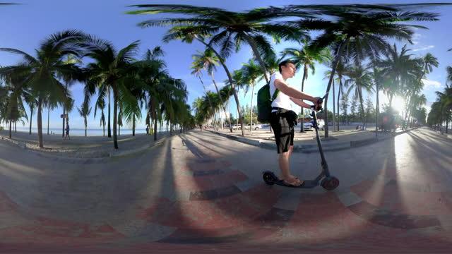 vídeos de stock e filmes b-roll de 360 male tourists riding e-scooter on the beach - panorama equiretangular
